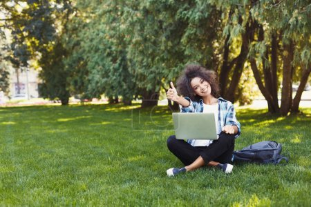 Photo for Happy casual african-american student girl with laptop outdoors. Smiling with computer showing thumb up, surfing the net or preparing for exams. Technology, success and remote working concept - Royalty Free Image