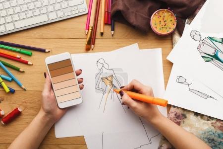 Photo pour Vue de dessus sur la créatrice de mode au travail. Mains féminines dessin de croquis de vêtements à son espace de travail créatif et en utilisant le smartphone avec les nuances de Brun dégradé de couleur sur l'écran, vue de dessus - image libre de droit