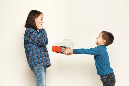 Photo pour Mignon petit garçon donnant à sa sœur cadeau, fond de studio blanc. Célébration d'anniversaire, frère félicitant sa soeur, espace de copie . - image libre de droit