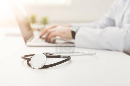 Photo for Stethoscope on white desk and doctor working on laptop in hospital, healthcare and medical concept, selective focus, closeup - Royalty Free Image