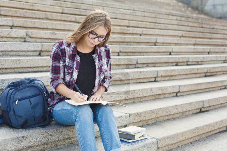 Photo for Young concentrated female freelancer making notes in notebook, sitting on university stairs. Education, inspiration and remote working concept. - Royalty Free Image