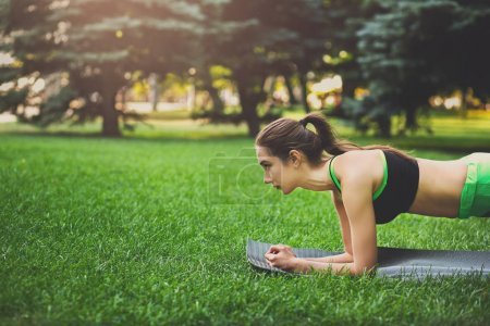 Frau trainiert Yoga in Plankenpose im Freien