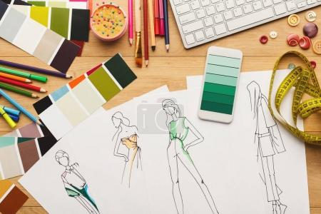 Photo for Creating new fashion collection background. Hand drawn sketches, smartphone with color swatches on screen and designer accessories on wooden table, top view. Creativity and dressmaking concept - Royalty Free Image