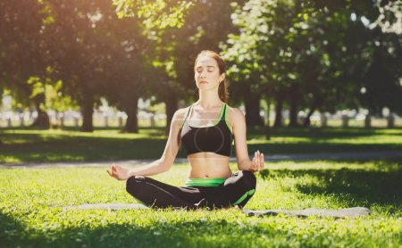 Photo for Young woman outdoors, meditation exercises. Girl doing lotus pose for relaxation with closed eyes. Wellness, calmness, relax, healthy, active lifestyle concept - Royalty Free Image
