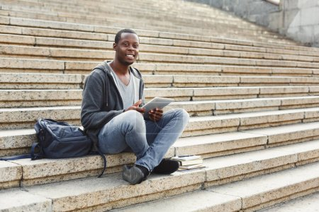 Photo for Happy african-american student sitting outdoors on university stairs with digital tablet, typing, surfing internet, preparing for exams. Technology, education and remote working concept, copy space - Royalty Free Image