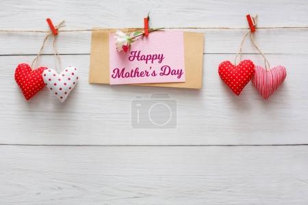 Mothers day background, heart and paper card on clothespins at wooden pillow hearts border on wood, copy space