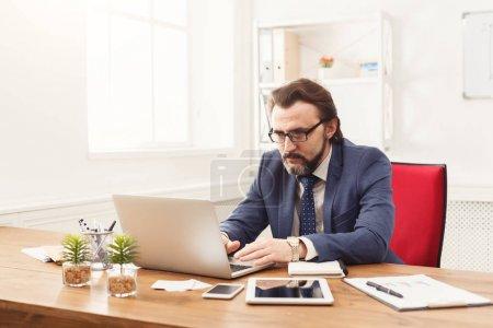 Photo pour Concentré, homme d'affaires travaillant sur ordinateur portable à l'intérieur moderne bureau blanc. Réfléchi employé au travail avec ordinateur, copie espace - image libre de droit