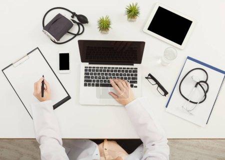 Photo pour Médecin assis au bureau avec du matériel médical tout autour, travaillant sur son ordinateur portable et des notes d'écriture, vue du dessus, espace de copie - image libre de droit