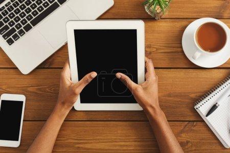 Photo pour Femelle noir mains sur tablette numérique avec écran blanc pour la publicité. Vue de dessus des mains afro-américaine, clavier d'ordinateur portable, smartphone, café sur un fond de table bureau en bois. - image libre de droit