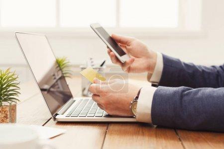 Photo pour Achats en ligne avec carte de crédit et portable, assis au bureau, le concept de commerce électronique, espace copie l'homme méconnaissable - image libre de droit