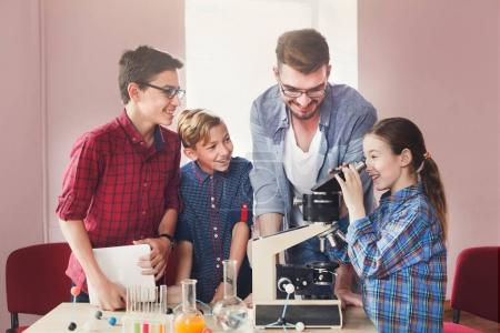 Photo for Teenagers with teacher making chemical experiment in laboratory with reagents and looking through a microscope. Early development, education, diy, innovation concept. Stem education. - Royalty Free Image
