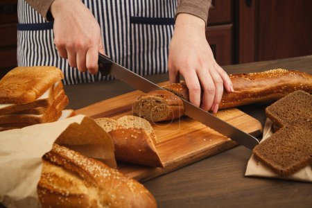 Photo for Woman cutting bread on wooden board. Unrecognizable female chef preparing healthy sandwiches, side view, copy space - Royalty Free Image