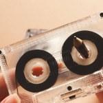 Hands rewinding magnetic tape audio cassette on pe...