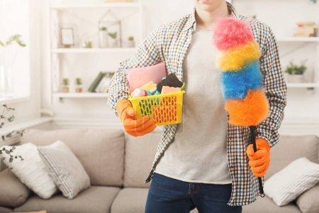 Photo pour Homme méconnaissable dans des gants en caoutchouc tenant seau en plastique avec brosses, éponges et brosse à plumes dans le salon, espace de copie. Concept ménage et nettoyage à domicile - image libre de droit