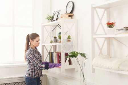 Photo for Woman cleaning dust from bookshelf. Young girl sweeping shelf, spring cleaning concept, copy space - Royalty Free Image