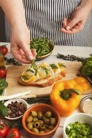 Photo for Female hands making bruschettas with cheese, lemon and arugula. Healthy vegetarian sandwiches at kitchen table with various vegetable bowls and greens. Cooking food background, closeup - Royalty Free Image