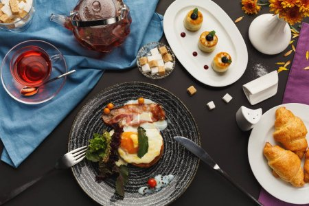 Photo for Restaurant delicious breakfast with sunny side up fried eggs, bacon, vegetables and greens, croissants and freshly brewed tea served on black table. Nourishing morning meals, top view - Royalty Free Image