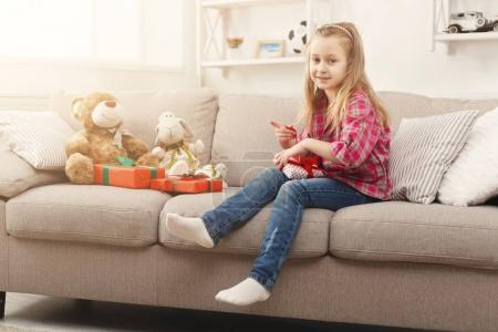 Photo for Happy little girl unpacking gifts. Beautiful child unwrap presents on sofa at home. Festive concept. International Womens Day, Christmas or birthday party - Royalty Free Image
