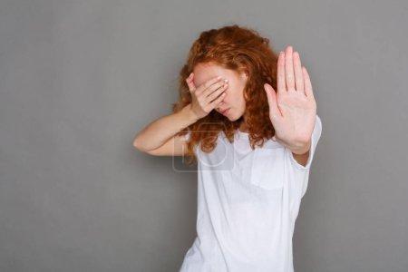 Foto de Mujer pelirroja que cubre su rostro con la palma y decir no. Gesto de parada haciendo de chica con su mano. Estudio disparo en fondo gris, espacio de copia. Ningún concepto mal y lenguaje corporal - Imagen libre de derechos