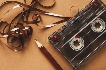 Retro audio cassette and pencil on light brown bac...