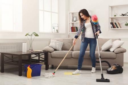 Photo pour Femme choquée maison avec beaucoup d'outils de nettoyage. Young fatigué plancher lavage fille avec mop et aspirateur, espace copie - image libre de droit