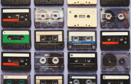 Photo for Retro audio cassette tapes on blue background. Top view on vintage media devices, copy space on labels, flat lay - Royalty Free Image