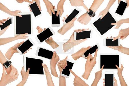 Photo pour Ensemble de mains blanches masculines et féminines touchant le téléphone portable et l'écran de la tablette et pointant avec l'index sur l'écran blanc avec espace de copie, fond blanc isolé. Concept de communication - image libre de droit