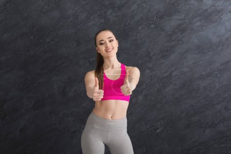 Photo for Happy sporty woman showing thumb up on grey background. Young beautiful fitness girl gesturing, copy space - Royalty Free Image