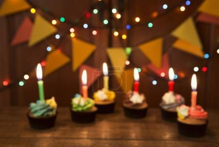 Photo for Chocolate cupcakes with colourful icing and candles against festive background with garland, unfocused. Birthday, party, holiday concept - Royalty Free Image