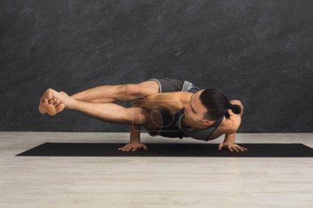 Photo pour Jeune homme fort pratique l'yoga, debout dans une posture souple sur mains sur tapis en cours de conditionnement physique, ce qui équilibre exercice, espace copie - image libre de droit