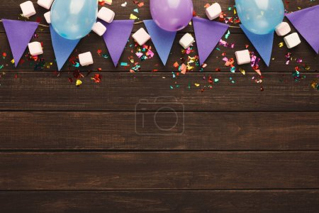 Photo for Violet paper flags garland and baloons on rustic wood. Birthday party decoration background, top view, copy space. Mockup for greeting card - Royalty Free Image