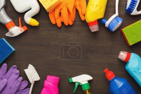 Photo pour Printemps nettoyage fond. Assortiment de détergents de pulvérisation colorés, éponges, chiffons et autres fournitures sur table en bois, vue de dessus. Services de nettoyage et de rangement concept, espace de copie - image libre de droit