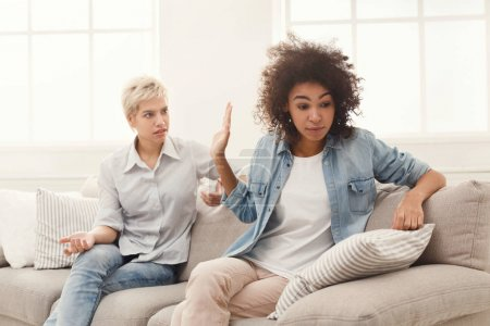 Photo for Two female friends sitting on sofa and arguing with each other. Friendship, quarrel, female disagreement, copy space - Royalty Free Image