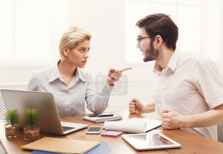 Photo for Emotional couple of young colleagues working in modern office. Two coworkers discussing work while sitting on workplace, copy space - Royalty Free Image