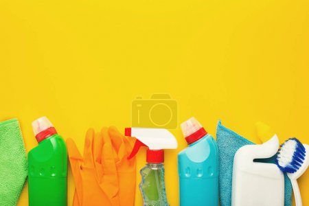 Photo for Spring cleaning background. Assortment of colorful spray detergents, sponges, rags and other supplies isolated on yellow. Cleaning services and tidying up concept, top view, copy space - Royalty Free Image