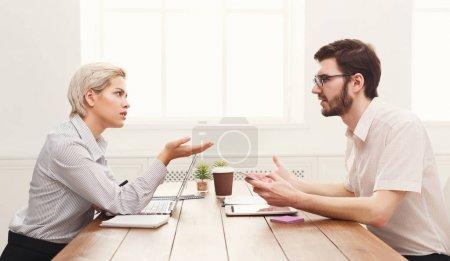 Photo pour Sérieux couple de jeunes collègues travaillant dans un bureau moderne. Deux collègues discutent du travail, de l'espace de copie, de la vue latérale - image libre de droit
