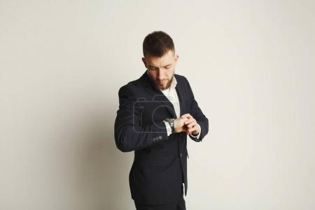 Photo for Handsome young caucasian businessman looking on watches, studio shot on white background. Confident serious man in formal clothes, copy space, isolated - Royalty Free Image