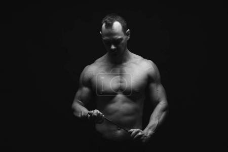 Photo for Strong athletic man, bodybuilder. Naked torso, muscular body. Strong chest and shoulder muscles. Studio shot, low key. Bodybuilding concept. Black and white image, copy space - Royalty Free Image
