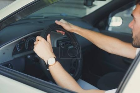 Photo for Closeup of male hands holding the steering wheel. Unrecognizable businessman sitting in car on driver seat, side view, copy space. Transport, business trip, speed and destination concept - Royalty Free Image