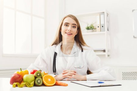 Photo for Nutritionist desk with healthy fruits, juice and measuring tape. Dietitian working on diet plan at office, smiling at camera. Weight loss and right nutrition concept - Royalty Free Image