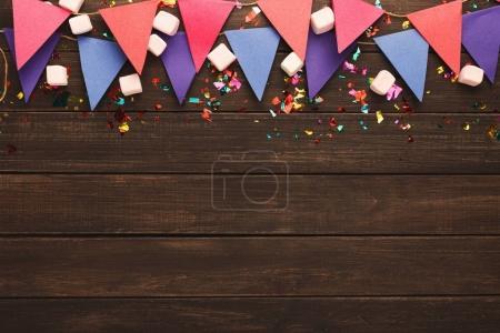 Photo pour Bordure de drapeaux en papier rose et violet guirlande, guimauves et confettis sur bois rustique. Décoration de fête d'anniversaire arrière-plan, vue de dessus, espace de copie. Maquette pour carte de vœux - image libre de droit