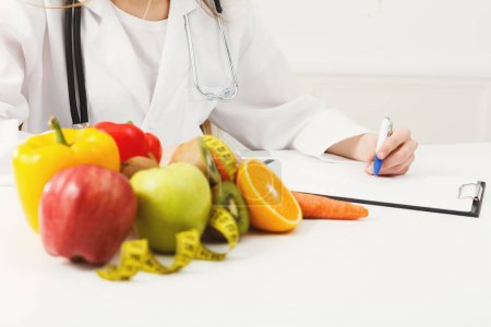 Photo pour Bureau nutritionniste avec fruits sains, jus et ruban à mesurer. Diététiste méconnaissable travaillant sur un plan de régime. Perte de poids et concept de bonne nutrition, orientation sélective - image libre de droit