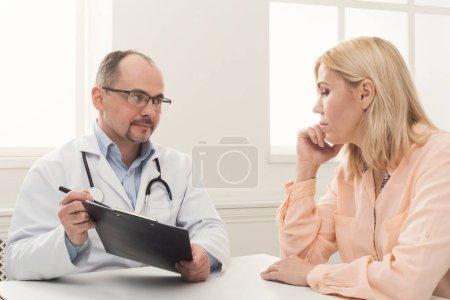 Photo pour Médecin sérieux consultant femme et montrant ses résultats de test, soins de santé et concept médical, espace de copie - image libre de droit