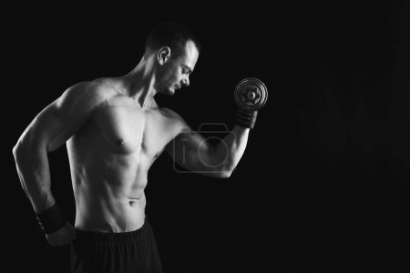 Photo for Athletic young man with dumbbell, black and white image. Naked torso, muscular body. Strong chest and shoulder muscles. Studio shot, low key. Bodybuilding concept, copy space - Royalty Free Image