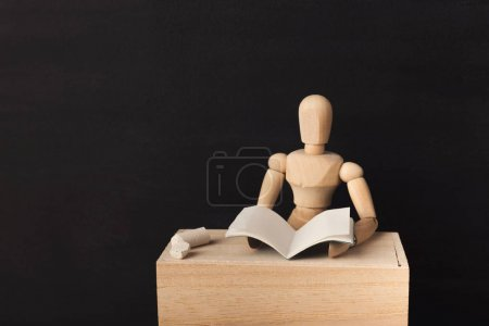 Wooden figure is reading a book against black background