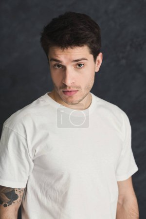 Photo for Handsome man in white t-shirt posing. Portrait of young confident guy, looking at camera, gray studio background - Royalty Free Image