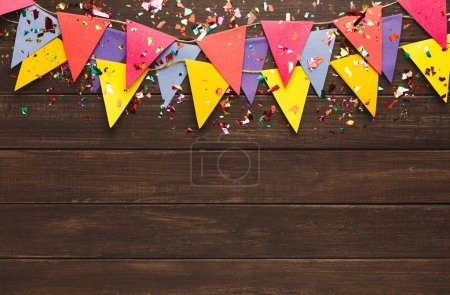 Photo for Border of colorful paper flags garland and confetti on rustic wood. Birthday party decoration background, top view, copy space. Mockup for greeting card - Royalty Free Image