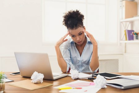 Photo for Deadline stress concept - sad african-american business woman sitting at desktop in office and holding hand on head. Hard working day, copy space - Royalty Free Image