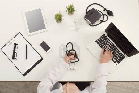 Photo pour Médecin assis au bureau avec équipement médical, tenant stéthoscope et pointant sur son ordinateur portable avec écran blanc, vue du dessus, espace de copie - image libre de droit