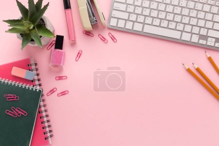Photo pour Blogueur beauté mode espace de travail avec clavier d'ordinateur portable, produits de maquillage, papeterie et bloc-notes sur fond rose. Lieu de travail gai avec espace de copie pour le texte, vue du dessus - image libre de droit